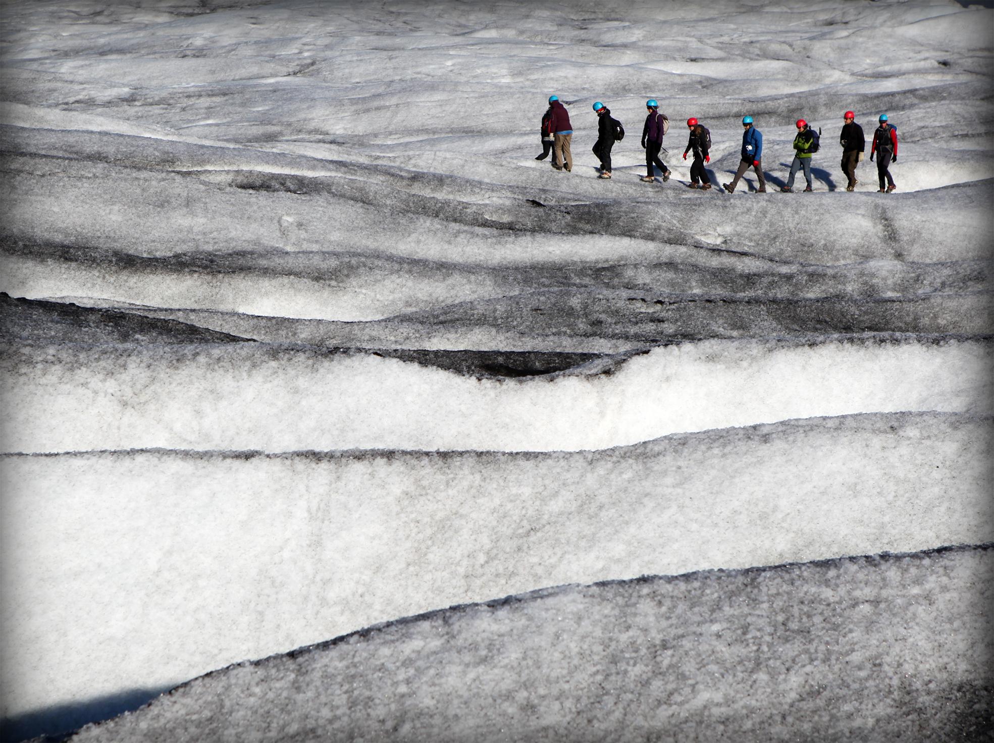 """Espectacular paseo por el glaciar Vatnajökull, paisaje grandioso, el cual te hace recordar un fragmento del libro de Barry López """"Sueños árticos"""" – """"….A veces tenemos una visión pasajera en campo abierto, un momento en que los contornos, los colores y el movimiento se intensifican y se nos revela un elemento sagrado que nos induce a creer en la existencia de otro espacio de realidad equivalente al espacio físico, pero distinto. El paisaje es como un poema: inexplicablemente coherente, trascendente en su significación y dotado del poder de trasladar a un plano más elevado las consideraciones sobre la vida humana…"""" CATEGORÍA: Espíritu de exploración."""