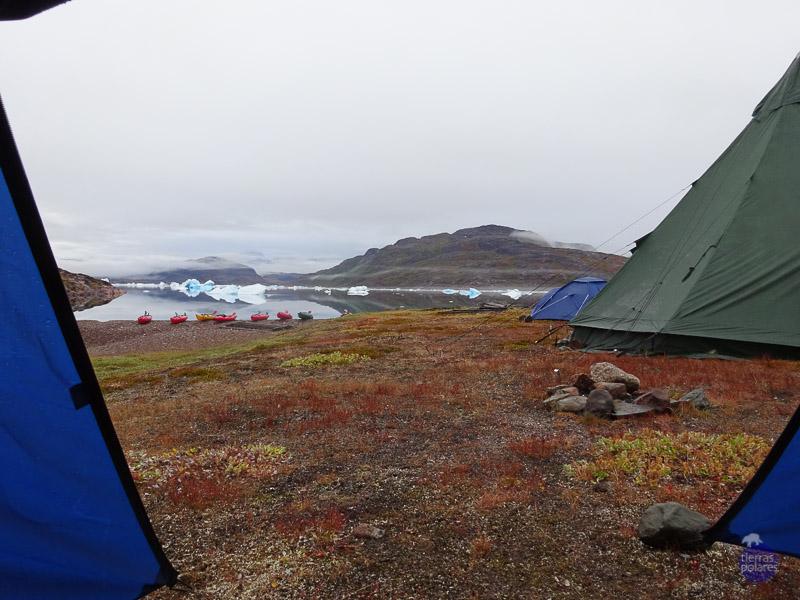 Viaje donde fue tomada la foto:  La ruta de Erik el rojo (Groenlandia) Breve descripción de la foto:  Son las 6 de la mañana, me despierto dentro de la tienda y compruebo, por la ausencia del ruido de las gotas al caer, que la lluvia de la noche anterior ha cesado. Decido abrir la cremallera de la tienda y contemplo maravillada, nuestros kayaks sobre la playa y la bahía  con  sus  icebergs  al  fondo,  en  un  silencio  absoluto.  Es  mi  segundo  día  en Groenlandia, ¡no puedo pedir más!  Categoría en la que participa:  Mi fotaza